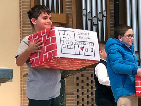 Caring For Others • Jackson Bahr, a second grade student in St. Joseph School student holds his brick that shows his Corporal Work of Mercy of Comforting the Sick. Photos courtesy of JoAnn D'Anton