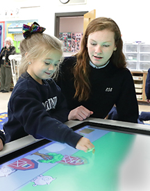 "This 2018 photo shows St. Dominic School, Brick, eighth grader Danielle Murat working with a kindergartner as she plays with a""farm""app during a Catholic Schools Week  Teacher Appreciation Day event in which eighth-graders became teachers for a day in St. Dominic School, Brick. Now as the 2019 Catholic Schools Week approaches, schools from around the Diocese are getting ready to host a week of activities which include welcoming potential students and their families for visits and tours of their facilities. John Blaine photo"