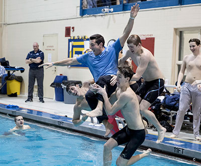 Coach Vito Chiaravalloti gets thrown into the pool after the Christian Brothers Academy swim team wins the NJSIAA Non-Public A title. John Blaine photo