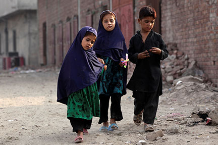 Afghan refugee children walk along a road in Lahore, Pakistan, June 20, which is World Refugee Day. Children younger than 18 make up one half of the world's refugee population, a U.N. report said. CNS photo/Mohsin Raza, Reuters