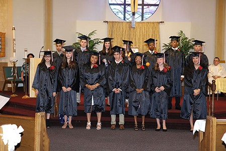 The 14 members of the Holy Innocents School's final graduating class stand before the altar of the Neptune church June 7. The school is closing this June.  John Batkowski photo