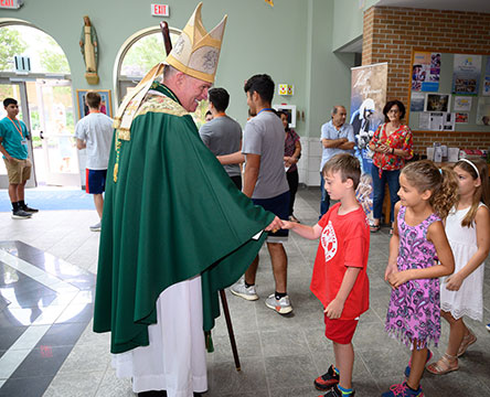 Following the Mass he celebrated in St. Benedict Church, Holmdel, Bishop David M. O'Connell, C.M., greets students who are particpating in the parish's Summer Academy religious education program. Mike Ehrmann photo