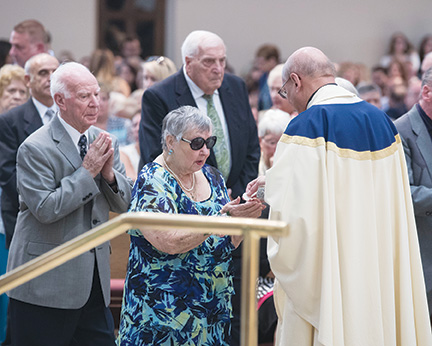 Ben and Frances Paolillo receive the Body of Christ during Communion. The couple, natives of Brooklyn, now attend St. Luke Parish, Toms River. Craig Pittelli photo