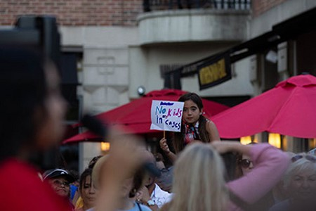 "A young girl holds a sign that reads, ""No kids in cages,"" during the Princeton vigil."