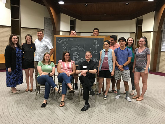 Father Patrick McPartland, seated right, joins with young adults from St. Catharine Parish, Holmdel, who participated in the Spiritual Boot Camp events that were held in late July. Courtesy photo