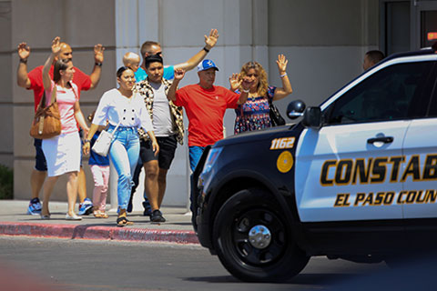 Shoppers exit with their hands up after a mass shooting Aug. 3 at a Walmart in El Paso, Texas. CNS photo/Jorge Salgado, Reuters