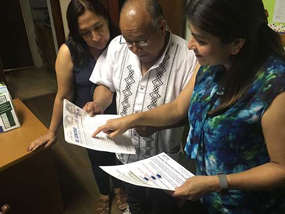 Sandra Pinto, client services coordinator for El Centro, looks over a mentor program information sheet with Agustíne Chavez and Monica Cabrera at the El Centro office in Trenton. Matt Greeley photo