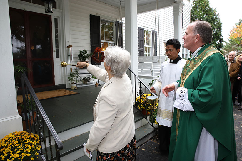 Sister of St. Joseph Marcy Springer sprinkles holy water on the front porch of Francis House of Prayer, Allentown. Bishop David M. O'Connell, C.M., was on hand Oct. 6 for an outdoor Mass celebrating the diocesan retreat house's new location. John Batkowski photo
