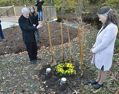 Father David Beaubien, pastor of St. Aloysius Gonzaga Church in Leonardtown, Md., offers a prayer Nov. 1, 2019, after a wreath of flowers was laid at the site where Benjamin Hance, a 22-year-old African American was lynched in 1887. Soil collected at the site was placed in two jars labeled with Hance's name. One jar will go to the National Memorial for Peace and Justice in Montgomery, Alabama, and the other will remain in St. Mary's County to educate the public about what happened there. At right is Karen Stone, the manager of the St. Mary's County Museum Division. CNS photo/Michael Hoyt, Catholic Standard