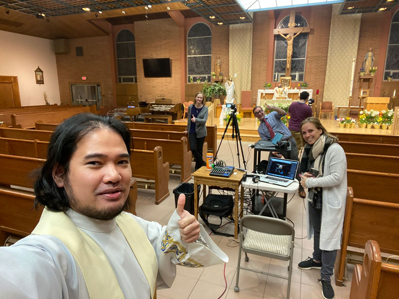 Father John Michael Patilla, parochial vicar of St. Benedict Parish, Holmdel, and staff members get ready to livestream during the Easter Triduum liturgies. Courtesy photo