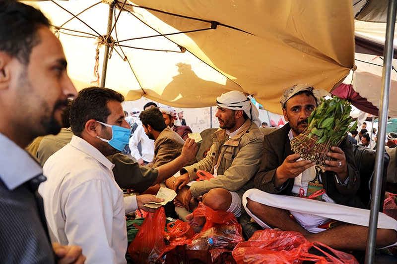 A vendor holds up an item June 7 at a market in Sanaa, Yemen, during the COVID-19 pandemic. CNS photo/Khaled Abdullah, Reuters