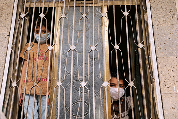 Children wearing protective masks look out the window of their home in Sanaa, Yemen, during the COVID-19 pandemic. CNS photo/Khaled Abdullah, Reuters