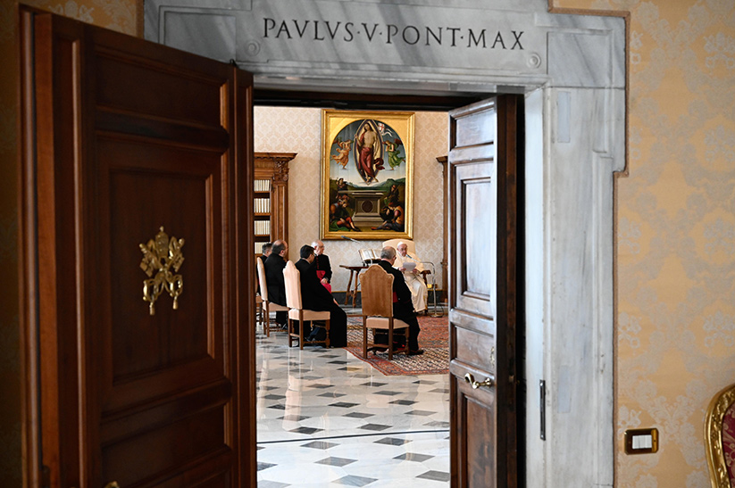 Pope Francis is pictured through a doorway as he leads his general audience in the library of the Apostolic Palace at the Vatican Dec. 9, 2020. The pope continued his series of talks on prayer, reflecting on prayers of petition. CNS photo/Vatican Media