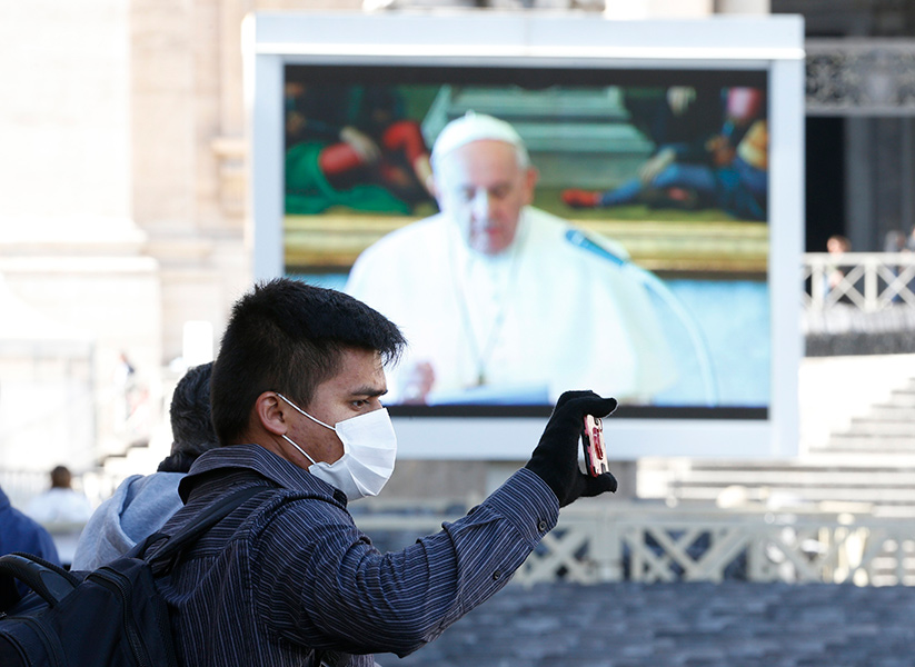 A man wearing a mask in St. Peter's Square takes a photo as Pope Francis appears on a video monitor leading the Angelus from his library in the Apostolic Palace at the Vatican in this March 8, 2020, file photo. The next day Italy and the Vatican began a nationwide COVID-19 lockdown that lasted into May.  CNS photo/Paul Haring