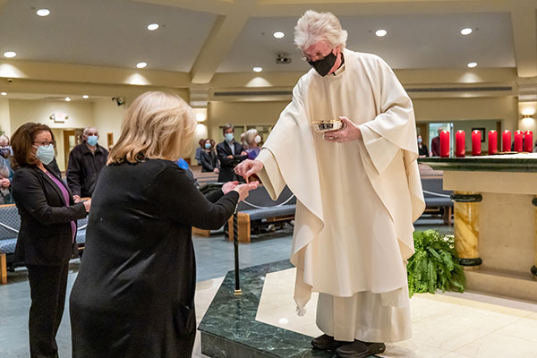 Father Timothy J. Capewell, parish pastor, distributes Holy Communion. Hal Brown photo