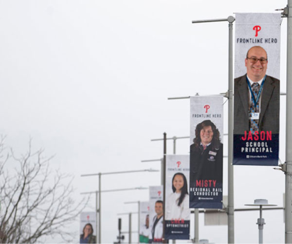 A photo of Dr. Jason Briggs, principal of St. Gregory the Great Academy, Hamilton Square, right, is displayed on a banner outside Citizens Bank Park – home of the Philadelphia Phillies. Courtesy photo